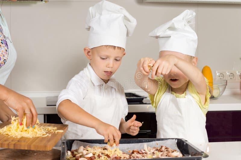 Leuke Kleine Jonge geitjes die Kaas op Pizza zetten royalty-vrije stock afbeelding