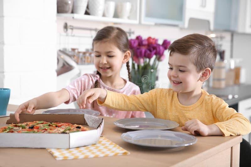 Leuke kleine jonge geitjes die smakelijke pizza eten stock fotografie