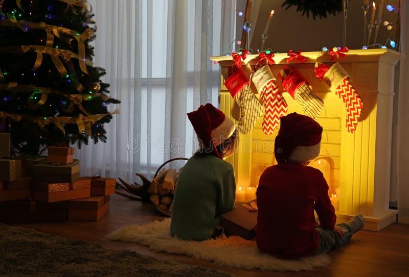 Leuke kleine jonge geitjes in Kerstmanhoeden die op deken dichtbij open haard thuis zitten royalty-vrije stock afbeelding