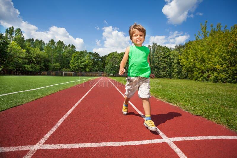 Leuke kleine jongenslooppas langzaam op de marathonweg stock foto's