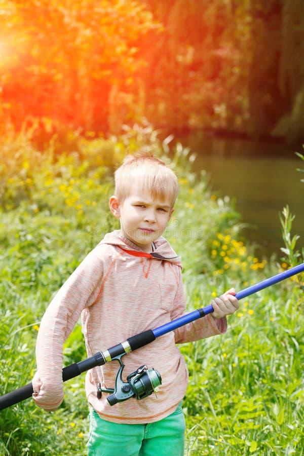 Leuke kleine jongenstribune dichtbij een rivier met een hengel in zijn handen royalty-vrije stock afbeeldingen
