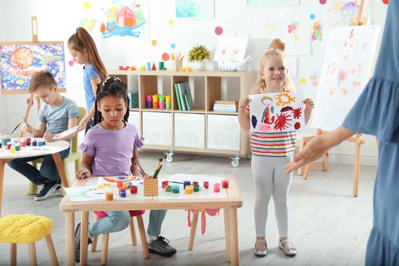 Leuke kleine kinderen bij het schilderen les stock afbeelding