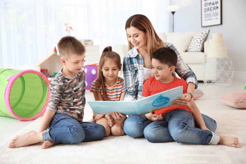 Leuke kleine kinderen die boek op vloer lezen stock foto