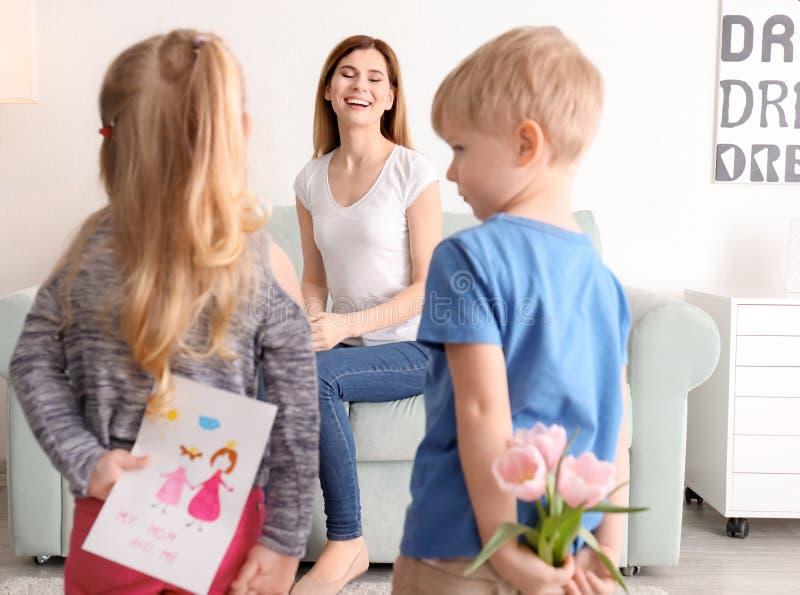 Leuke kleine kinderen die giften voor moeder achter hun rug verbergen stock afbeeldingen