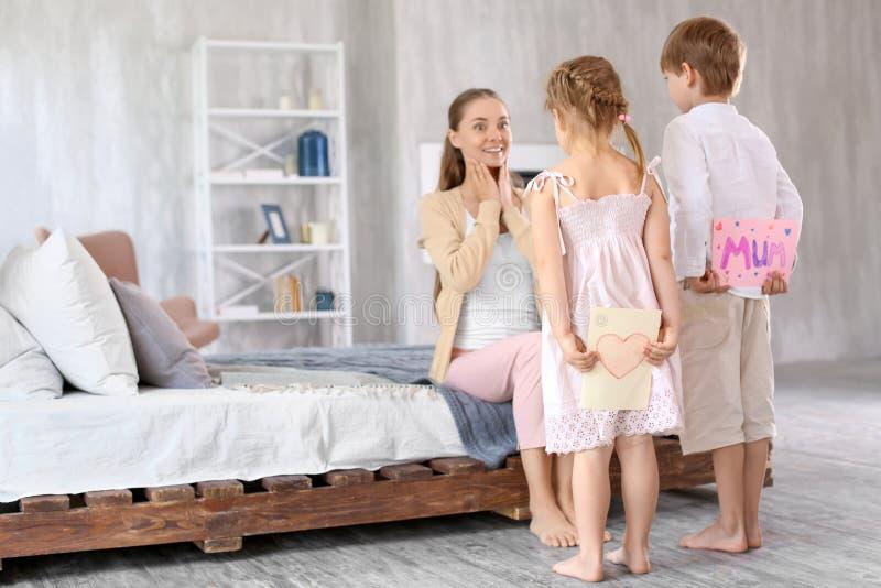 Leuke kleine kinderen die groetkaarten voor hun moeder achter rug thuis verbergen royalty-vrije stock afbeeldingen