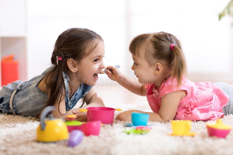 Leuke kleine kinderen die met keukengerei spelen terwijl thuis het liggen op vloer royalty-vrije stock fotografie