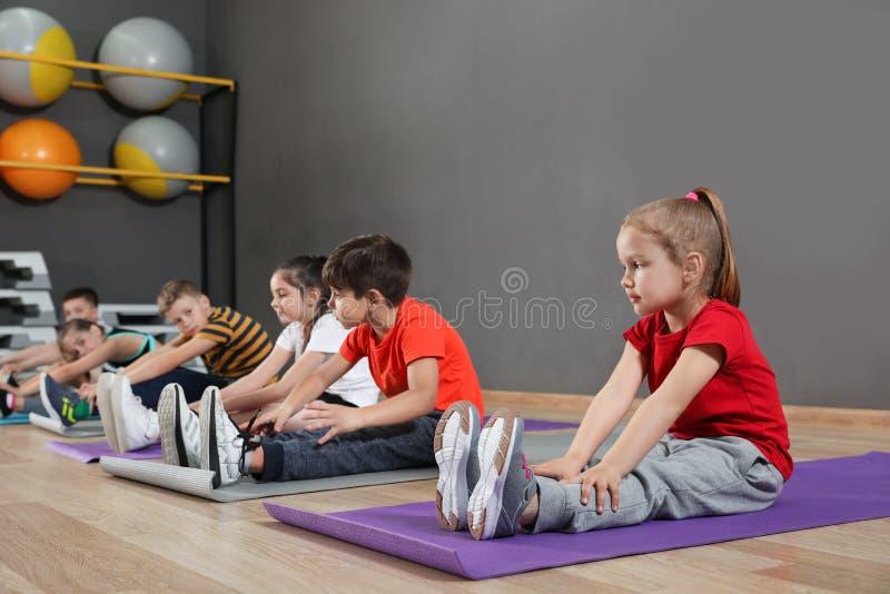 Leuke kleine kinderen die op vloer zitten en lichaamsbeweging in schoolgymnastiek doen royalty-vrije stock foto's