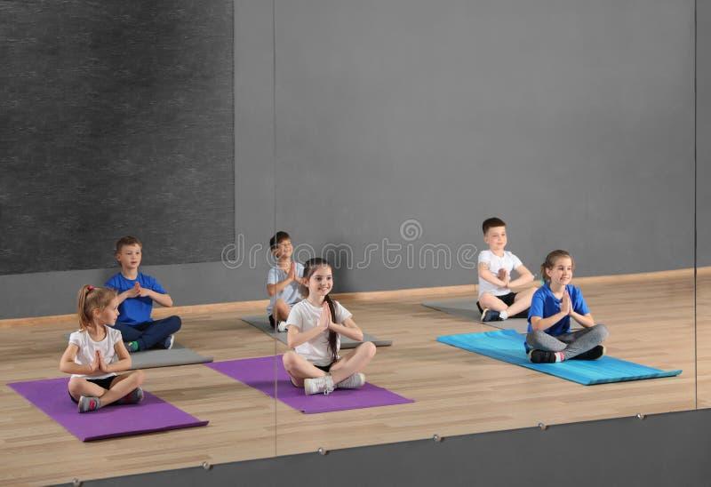 Leuke kleine kinderen die op vloer zitten en lichaamsbeweging in schoolgymnastiek doen stock afbeelding