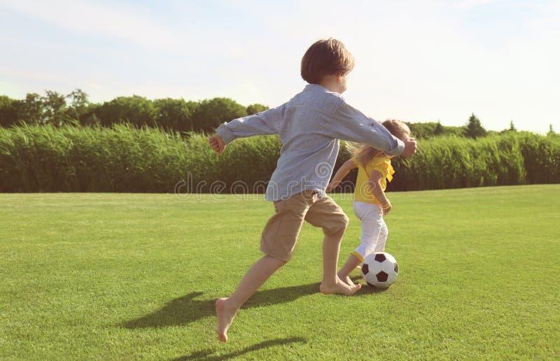 Leuke kleine kinderen die voetbal in park op zonnige dag spelen royalty-vrije stock afbeelding