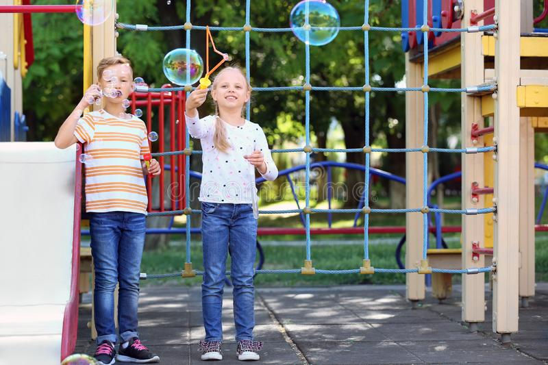 Leuke kleine kinderen die zeepbels in openlucht op speelplaats blazen royalty-vrije stock afbeelding