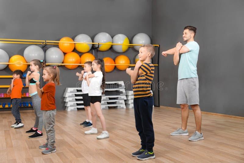 Leuke kleine kinderen en trainer die lichaamsbeweging in schoolgymnastiek doen royalty-vrije stock foto