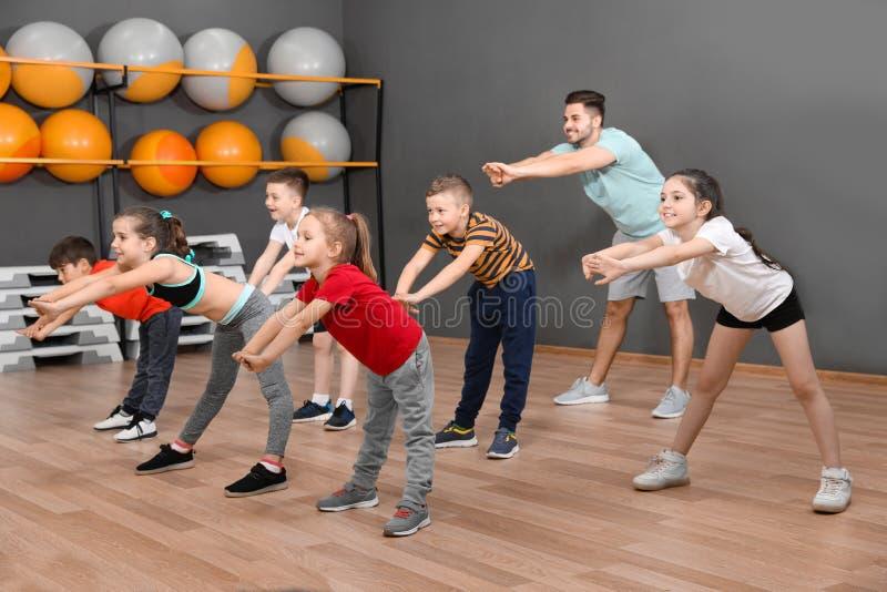 Leuke kleine kinderen en trainer die lichaamsbeweging in schoolgymnastiek doen stock afbeelding