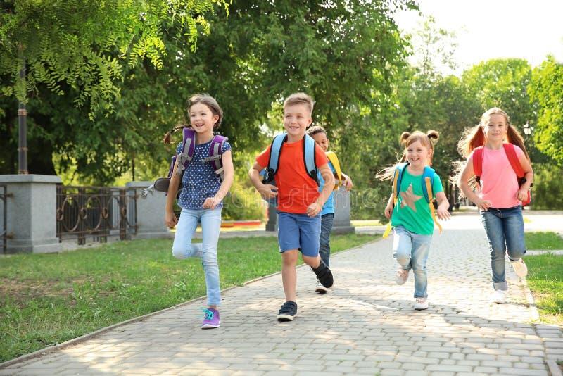 Leuke kleine kinderen met rugzakken die in openlucht lopen royalty-vrije stock afbeelding