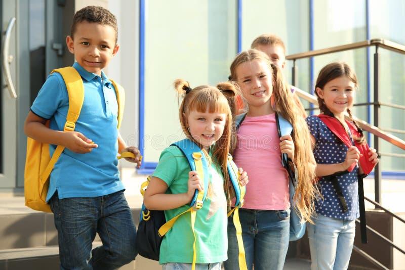 Leuke kleine kinderen met rugzakken in openlucht stock fotografie
