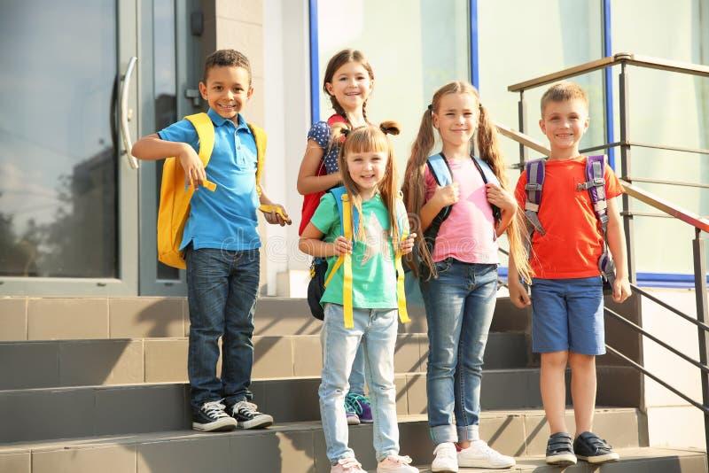 Leuke kleine kinderen met rugzakken in openlucht stock afbeelding