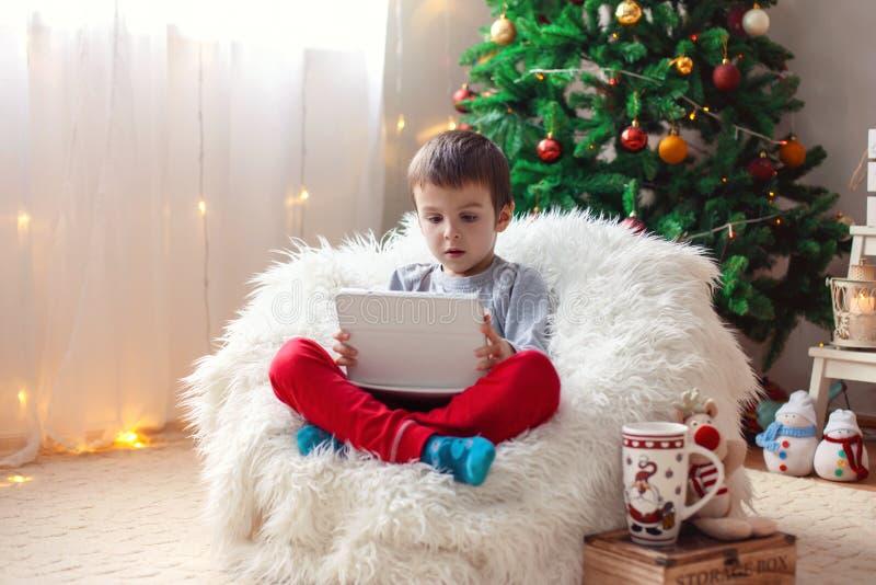 Leuke kleine zieke jongen, die op kinderspel zitten, die op tablet spelen stock fotografie