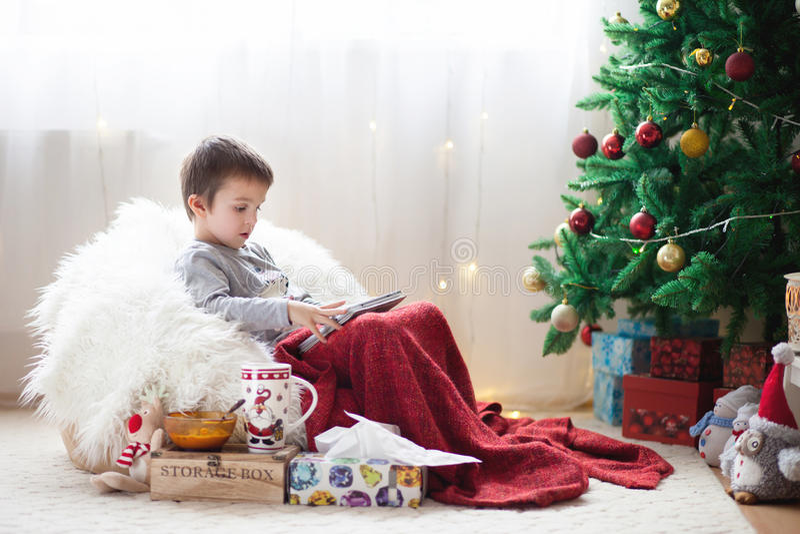 Leuke kleine zieke jongen, die op kinderspel zitten, die op tablet spelen en royalty-vrije stock fotografie