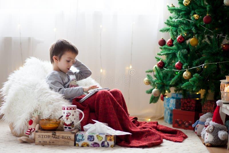 Leuke kleine zieke jongen, die op kinderspel zitten, die op tablet spelen en stock foto's