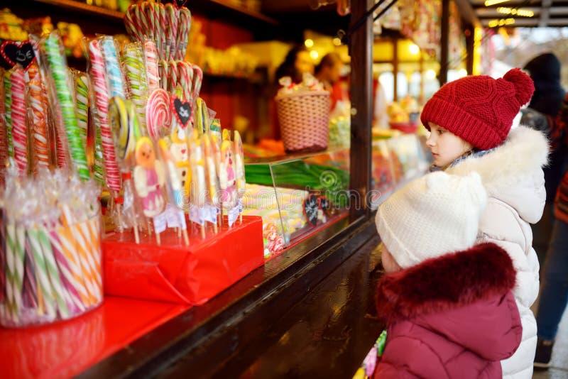Leuke kleine zusters die snoepjes op traditionele Kerstmismarkt kiezen op koele de winterdag royalty-vrije stock foto's