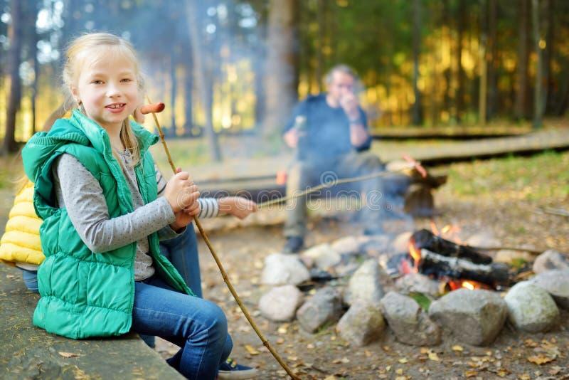 Leuke kleine zusters en hun vader roosterende heemst op stokken bij vuur Kinderen die pret hebben bij kampbrand Het kamperen met stock foto's