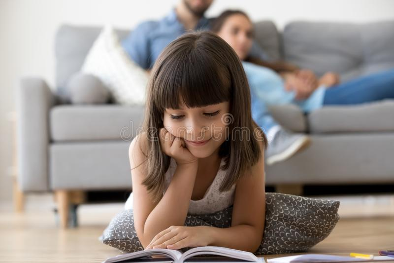 Leuke kleuter die op vloer liggen die interessant boek lezen stock foto's