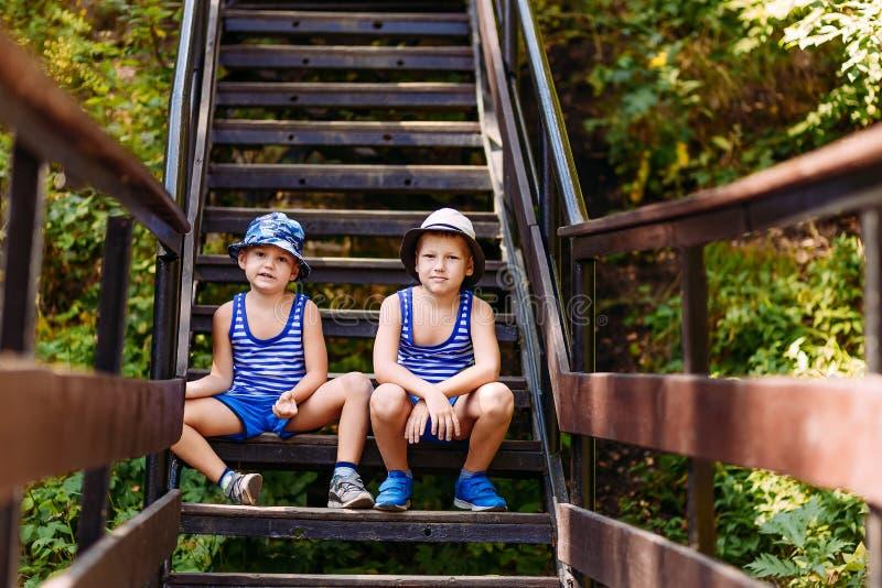 Leuke kleuterjonge geitjes in t-shirts, tennisschoenen en hoeden die op de stappen in de zomer zitten stock afbeeldingen