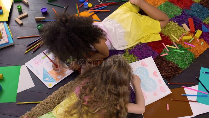 Leuke krullende multiraciale meisjes die op vloer liggen en met kleurenpotloden trekken royalty-vrije stock foto's
