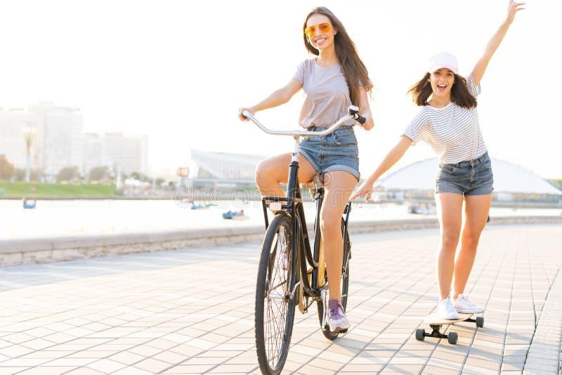 Leuke lachende jonge vrouw in jeansborrels op fiets die meisjesholding trekken terwijl het gebruiken van skateboard royalty-vrije stock foto's