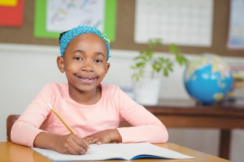 Leuke leerling die bij haar bureau in een klaslokaal werken stock afbeeldingen