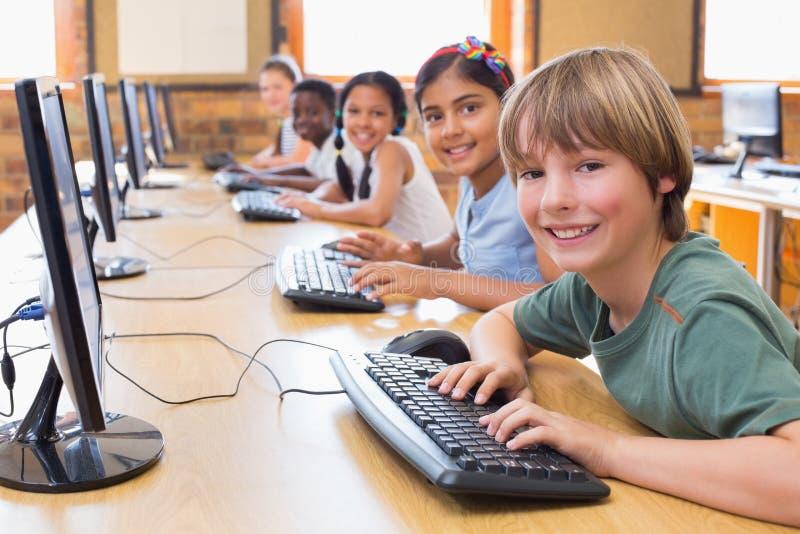 Leuke leerlingen in computerklasse stock fotografie