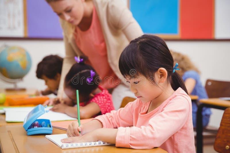 Leuke leerlingen die bij bureau in klaslokaal schrijven royalty-vrije stock foto's