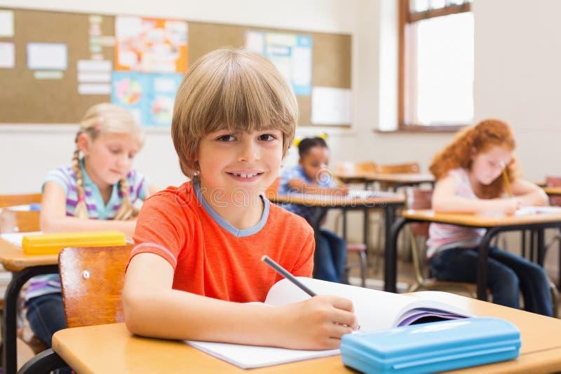 Leuke leerlingen die bij bureau in klaslokaal schrijven royalty-vrije stock afbeeldingen