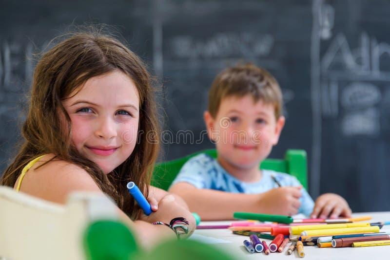 Leuke meisje en jongen die en met kleurrijke tellerspennen bij kleuterschool trekken schilderen De creatieve club van activiteite royalty-vrije stock afbeelding