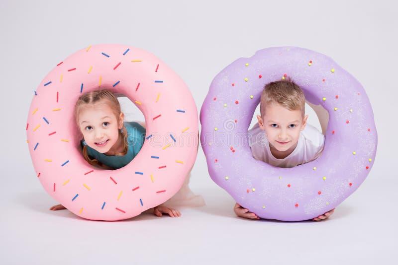 Leuke meisje en jongen met reusachtige donuts over wit stock foto's