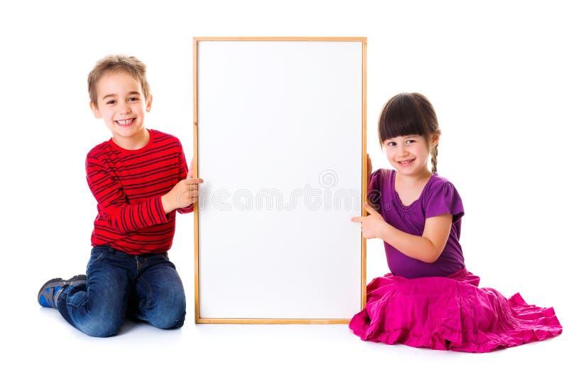 Leuke meisje en jongenszitting dichtbij lege advertentie stock afbeeldingen