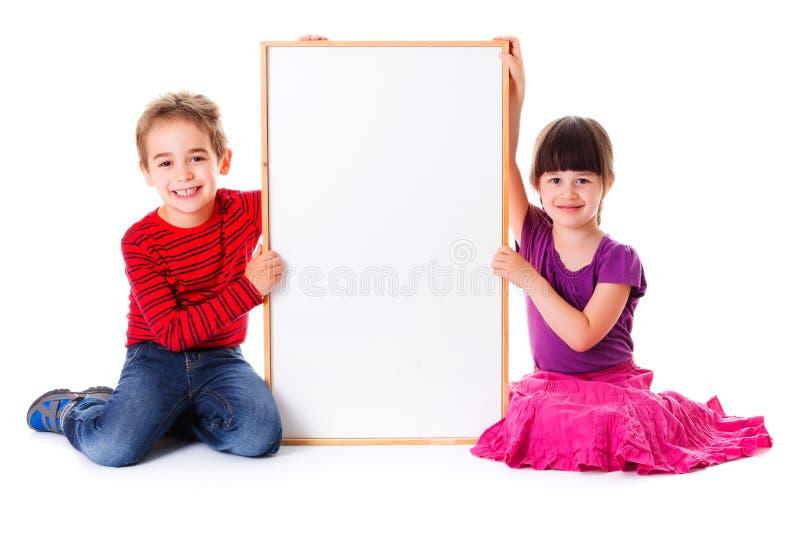 Leuke meisje en jongenszitting dichtbij lege advertentie stock foto