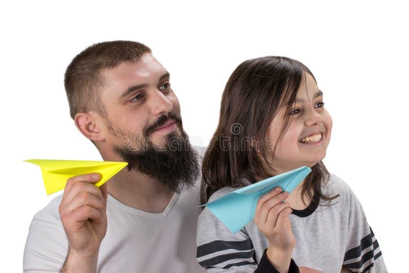 Leuke meisje en vader en het spelen met stuk speelgoed document vliegtuigisola royalty-vrije stock afbeeldingen