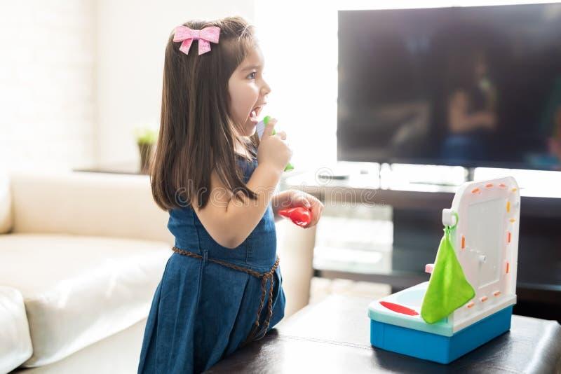 Leuke meisje het borstelen tanden met stuk speelgoed borstel stock afbeeldingen