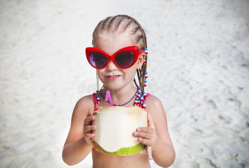 Leuke meisje het drinken kokosnotencocktail op tropisch strand stock foto's