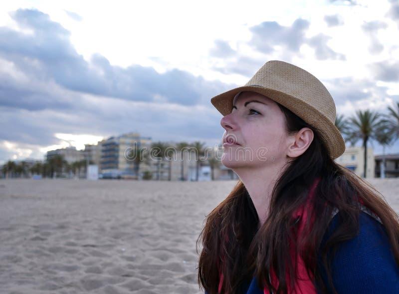 Leuke meisje het dromen zitting op het strand royalty-vrije stock afbeeldingen