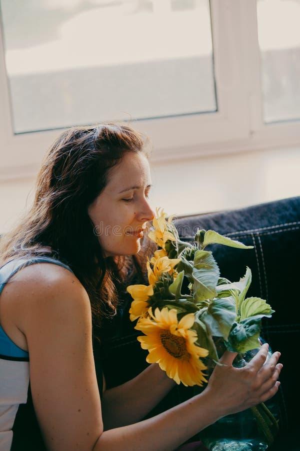 Leuke meisje het snuiven zonnebloemen voor het venster stock afbeelding
