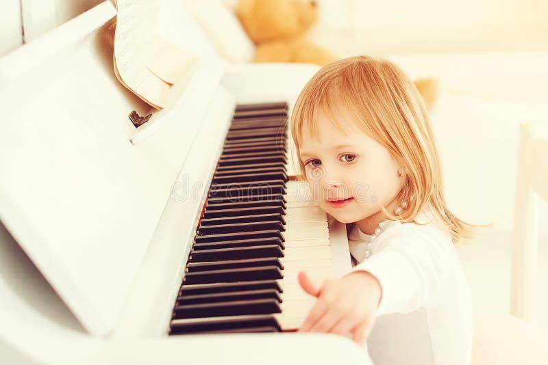 Leuke meisje het spelen piano op een muziekschool Peuterkind die muziekinstrument leren te spelen Onderwijs, vaardighedenconcept  stock afbeeldingen