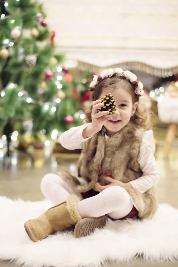 Leuke meisje het vieren Kerstmis thuis Zij zit op een stoel en houdt een nette kegel in haar handen Positieve emoties stock foto