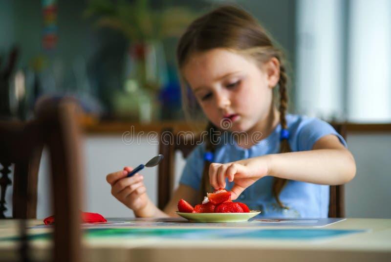 Leuke meisje proevende aardbei thuis stock afbeelding