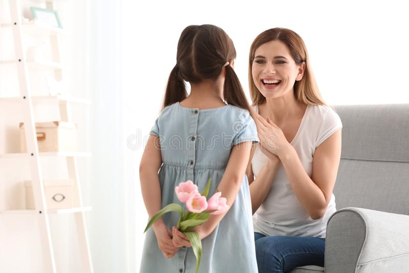 Leuke meisje verbergende bloemen voor moeder achter haar terug royalty-vrije stock fotografie