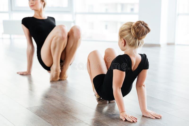 Leuke meisjeballerina en haar leraar die op vloer dansen stock fotografie