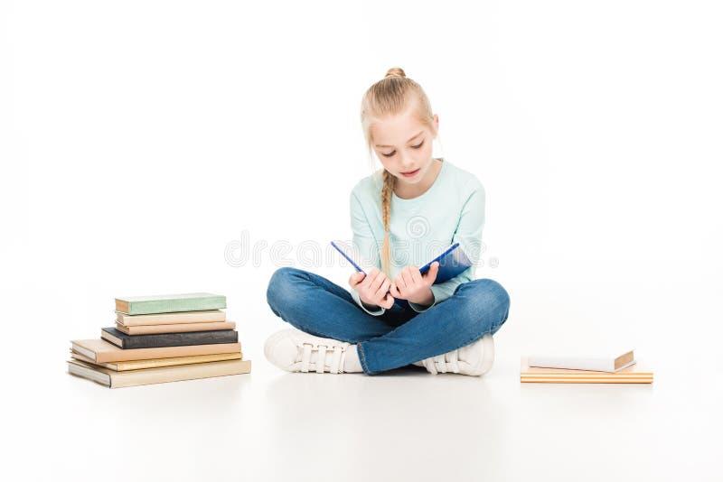 leuke meisjelezing terwijl het zitten tussen boeken royalty-vrije stock foto's