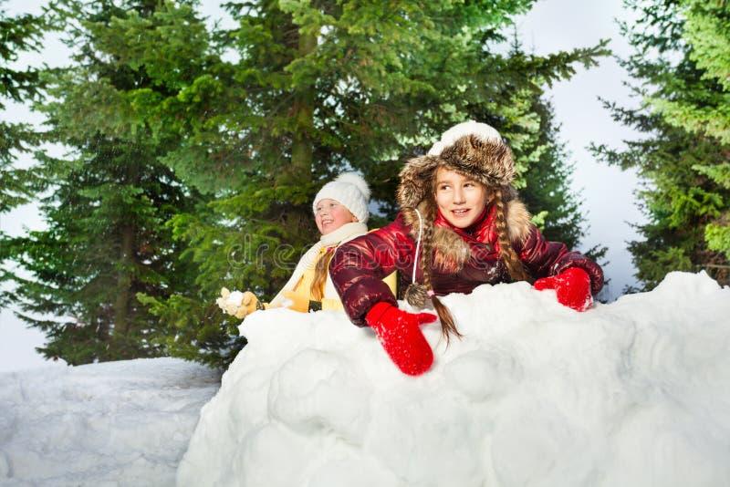 Leuke meisjes die de sneeuwballen op de dag van de winter spelen royalty-vrije stock foto