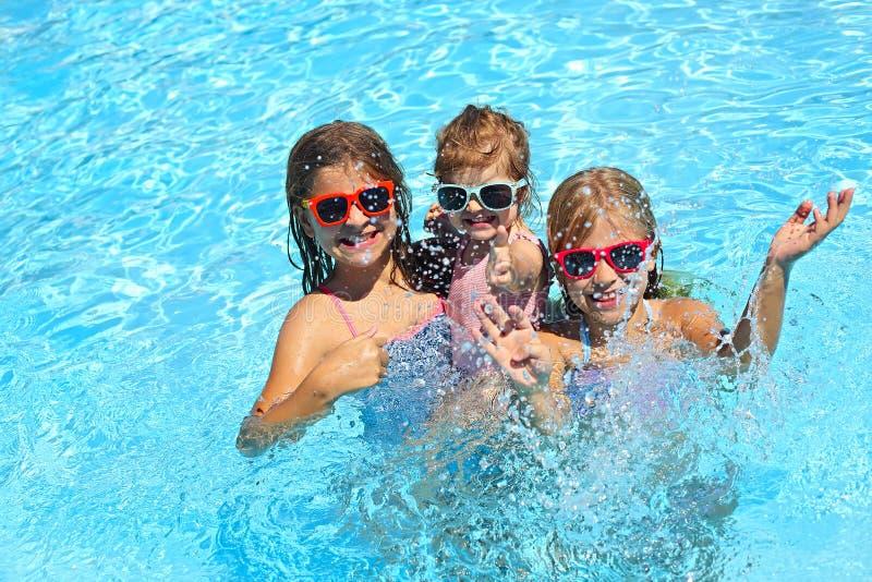 Leuke meisjes die in zwembad spelen De zomervakantie en reisconcept stock afbeelding