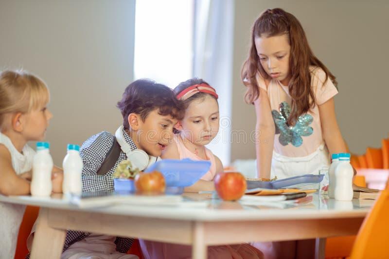 Leuke meisjes en jongen die de programmazitting bekijken in kantine royalty-vrije stock afbeeldingen